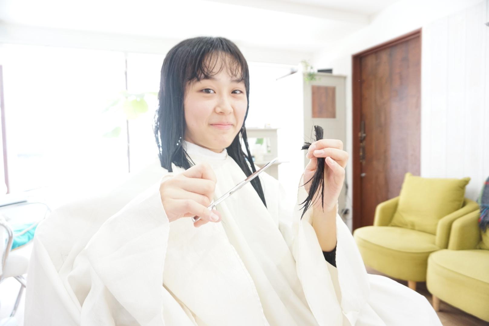 鋏で自分の髪を切る女性